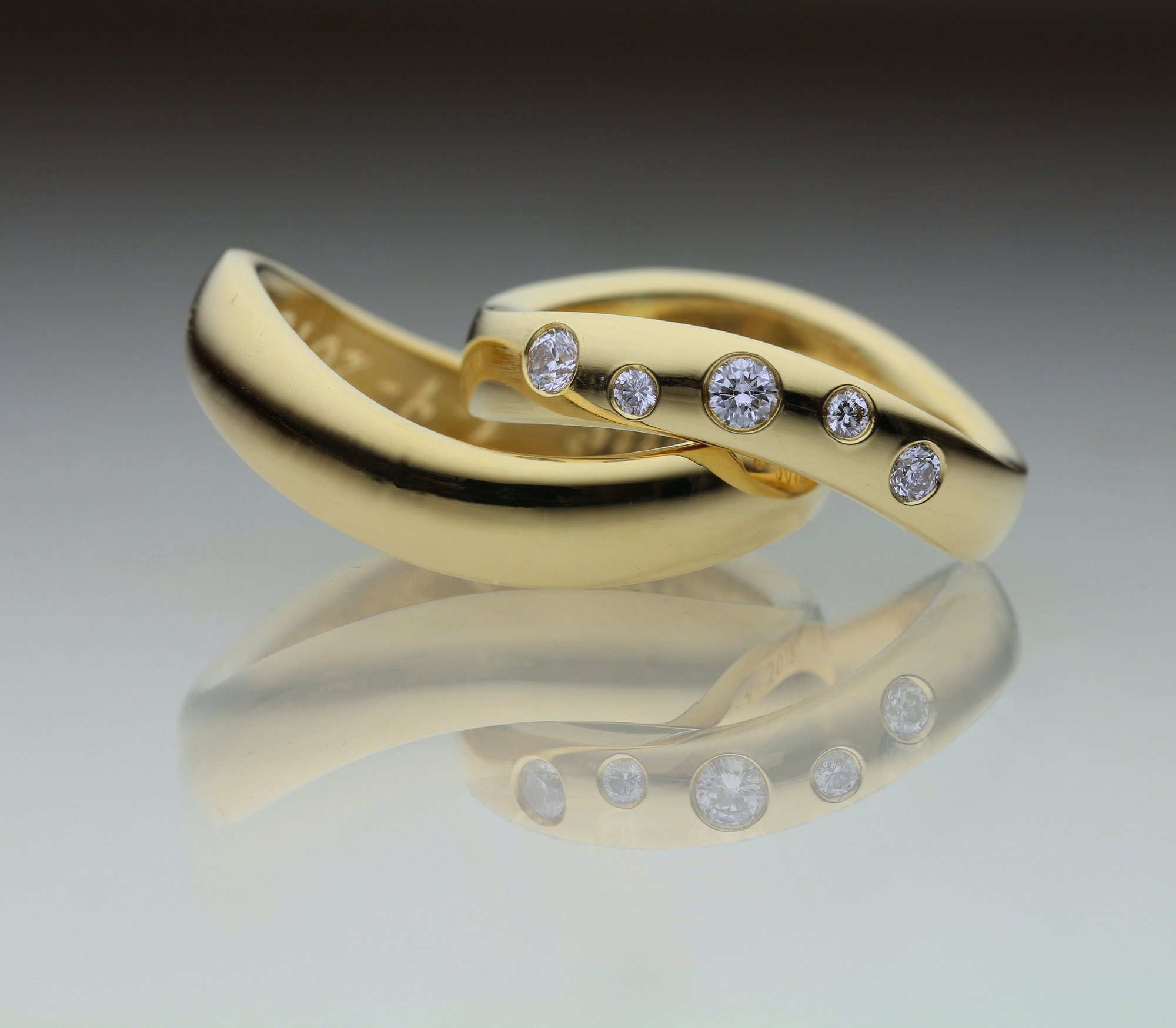 Forlovelsesring med buet blank overflade i guld med diamanter