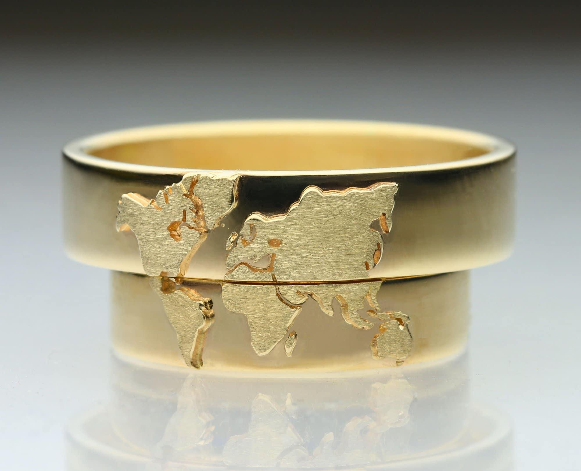 Vielsesringe i guld med mønster af verden